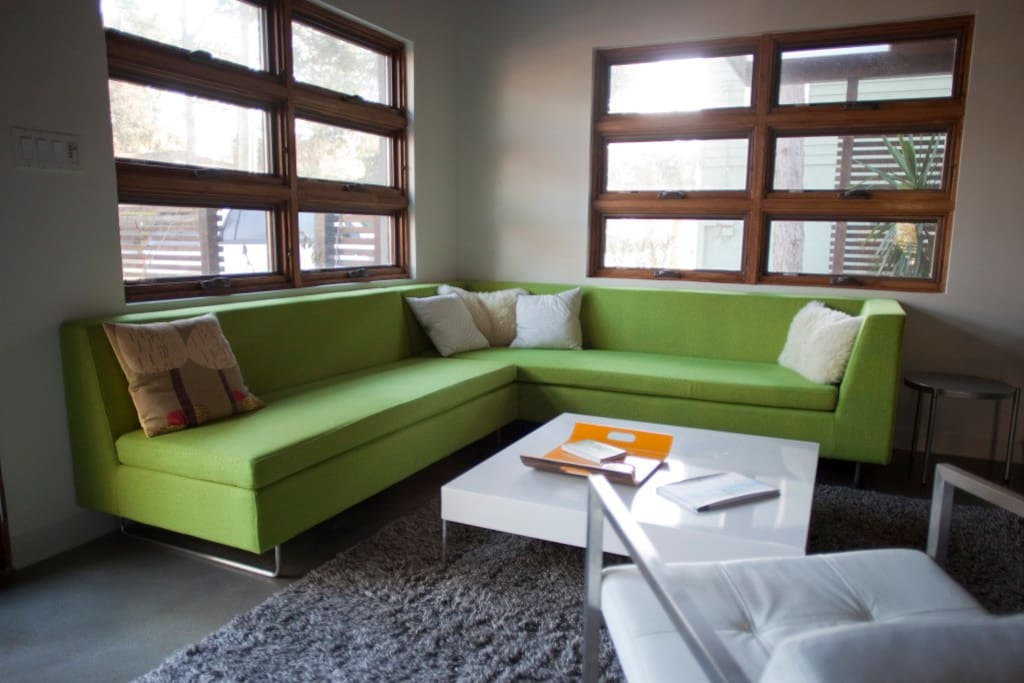 Giant green couch in living room, open to kitchen and facing big screen tv.