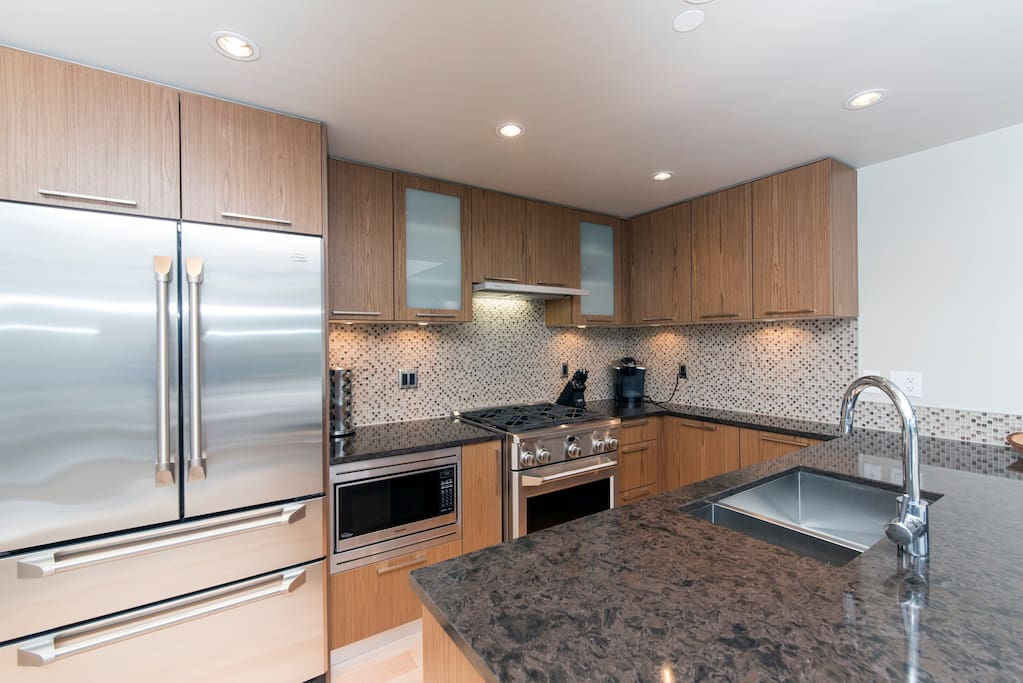 Gourmet kitchen with high end appliances including gas range stove and full sized dishwasher