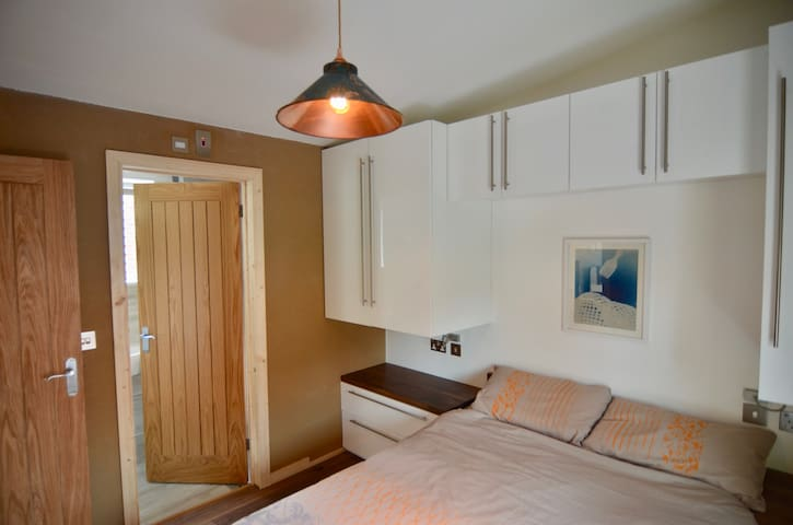Bedroom has clay plaster walls and bespoke space saving furniture.