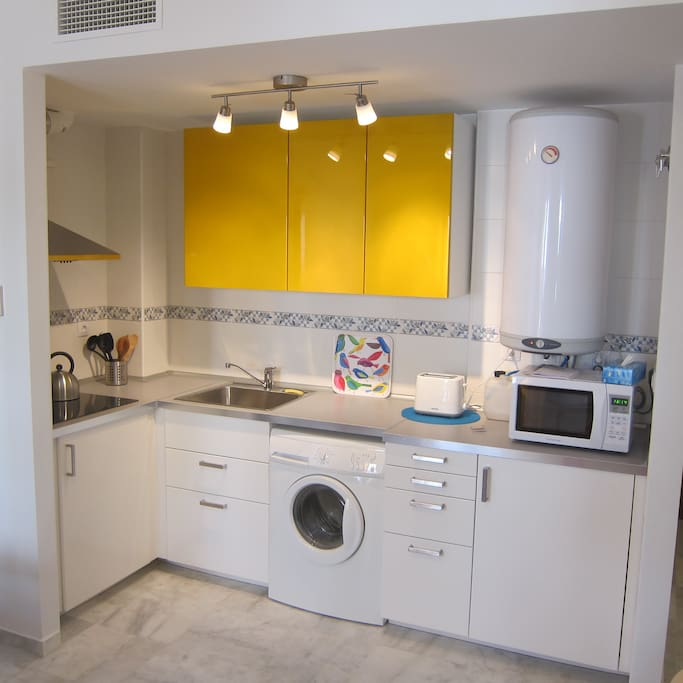Fully-furnished kitchen area. Electric induction stove-top. Stainless-steel sink. Clothes washing machine. Refrigerator. Microwave. Dishware. Cookware. Glasses. Flatware.