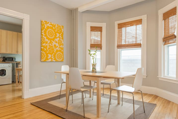 Large airy dining room with table that seats six.