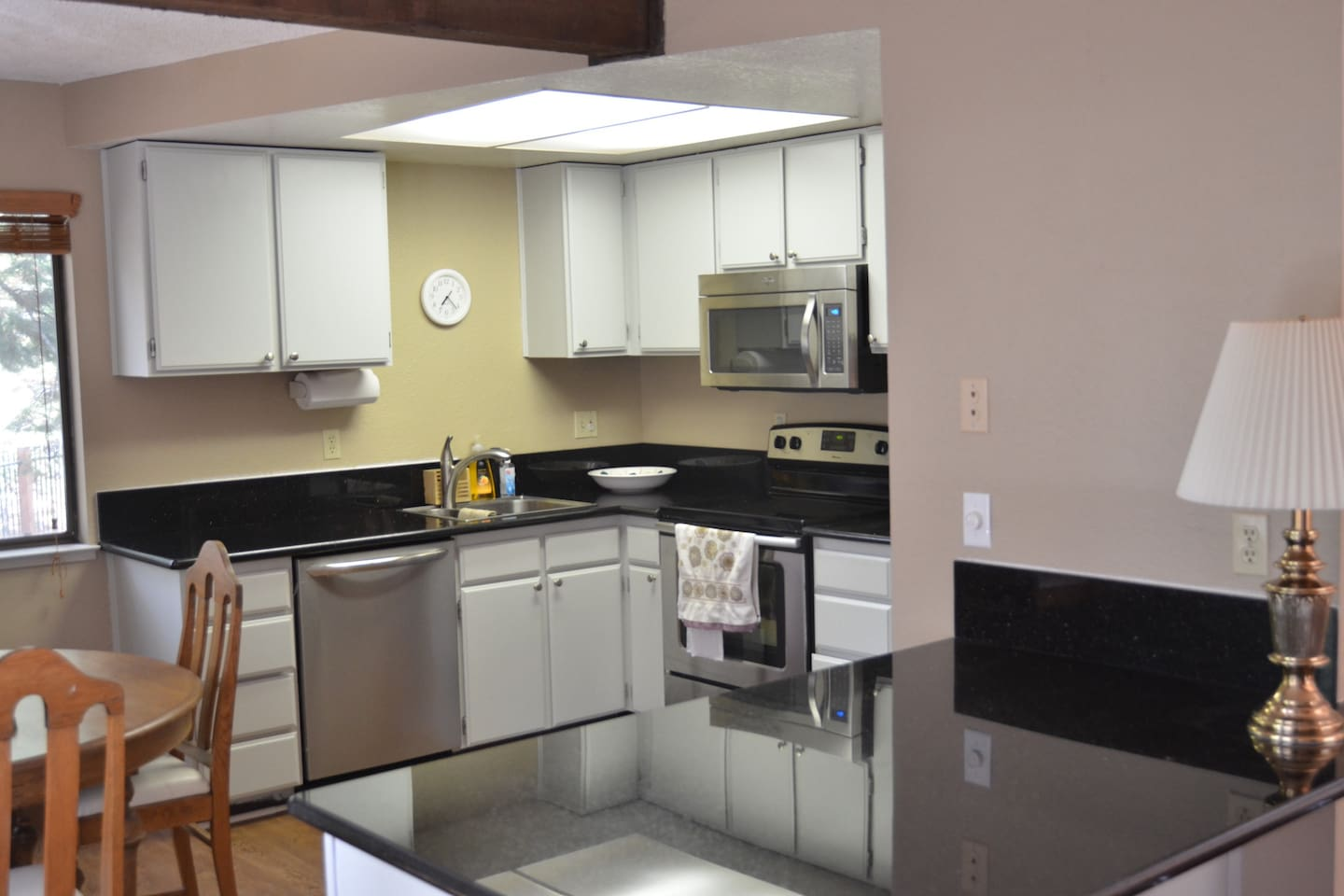 Eat in kitchen with granite counters and stainless steel appliances