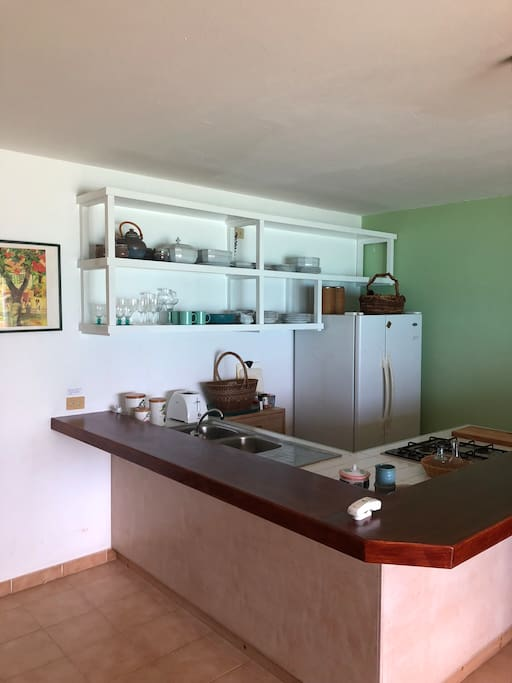 Equipped open kitchen with wrap around breakfast bar.