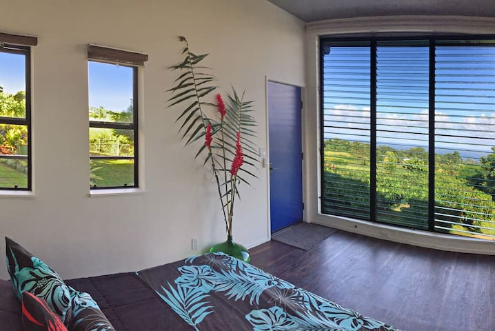 Cacao-Ocean Room: Surrounded by large windows overlooking the ocean and cacao orchard, enjoy whale watching from your bed in the winter months.