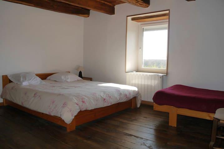 Chambre 3 avec 1 très grand lit et 1 petit lit.