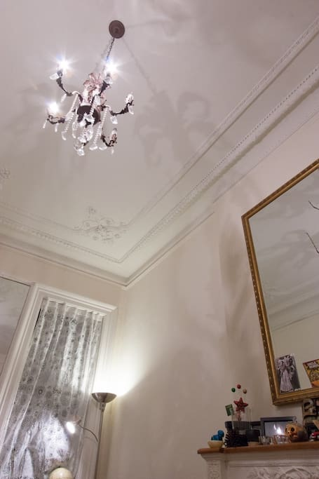 High ceilings are graced by original metal work and a large central chandelier.