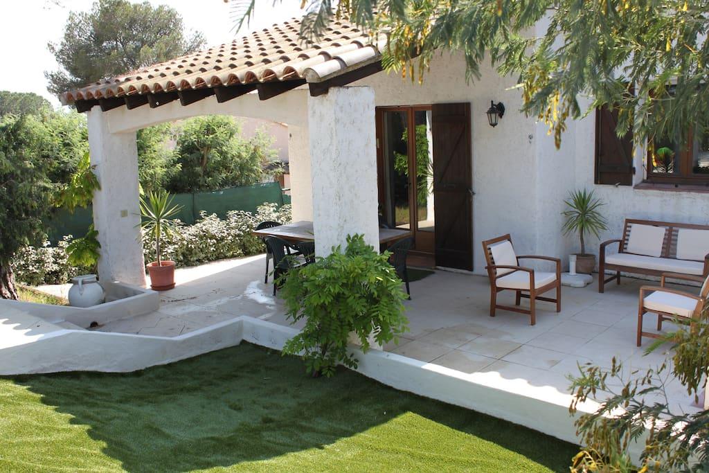 Aperçu de l'arrière de la villa et de sa terrasse ombragée