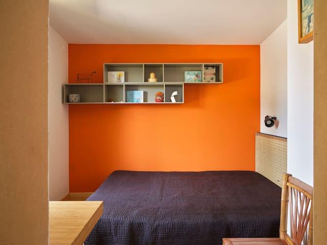 la petite chambre orange et son lit double.