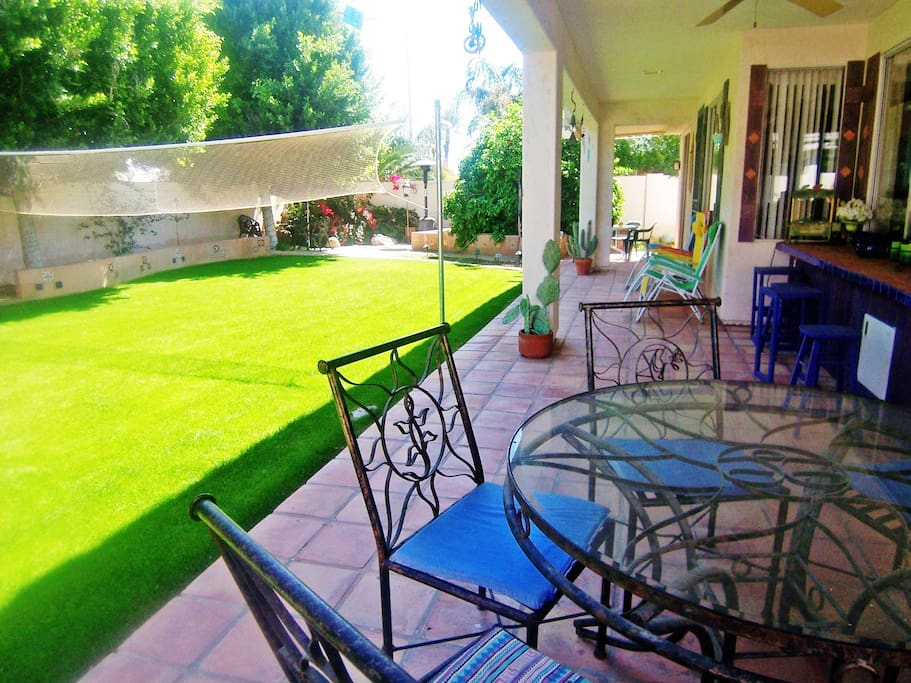 patio with tiled bar, large backyard with volleyball