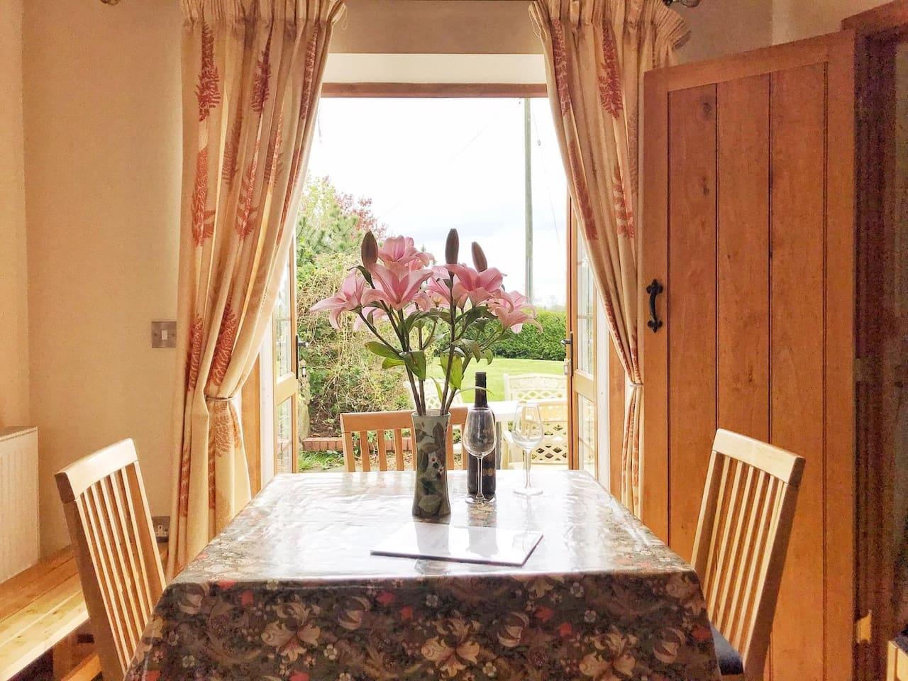 Dining area with double doors opening onto the patio and lawn area with far reaching views - perfect for sunny days and evenings and for children to play.