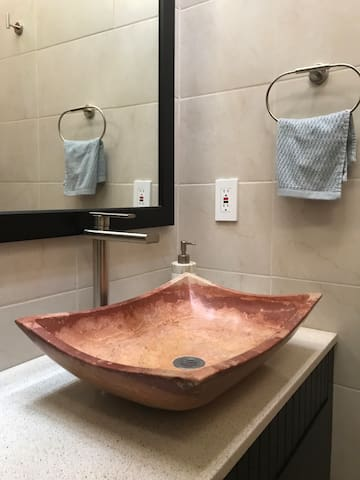 El bano de la recamara Lirio esta hermosamente decorado con materiales locales y bellos accesorios.   The  bathroom is beautifully decorated with local materials.