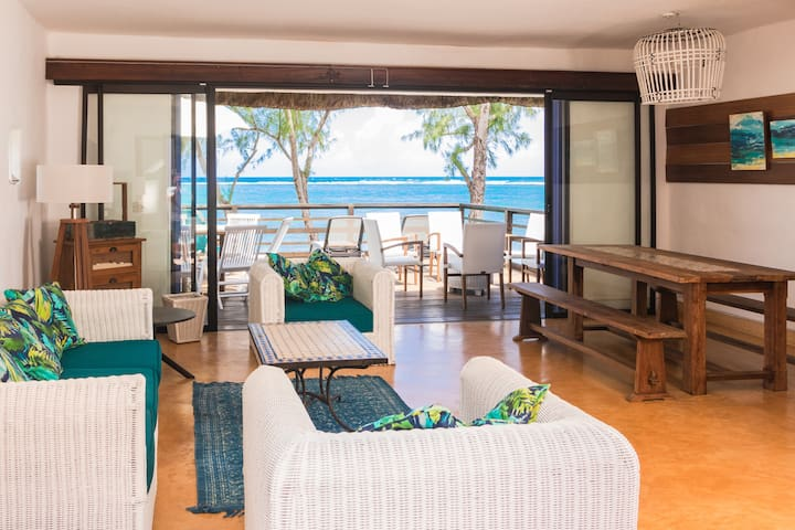 Living and dining room with access on a wooden deck overlooking 180 degrees of the turquoise lagoon