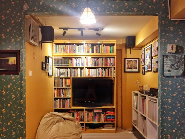 Living room with a rug, bookshelves, 2 bean bags, 1 record player
