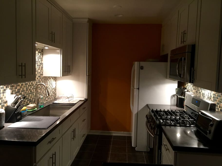 The kitchen with no lights on but little dimmers under cabinets and microwave.