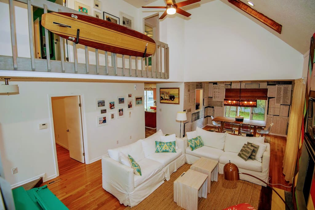 The great room - one of the white couches is a foldout. Downstairs bedroom door is pictured at left with dining room in rear and kitchen in left rear.  If you have little ones please note the slats on the upstairs balcony.