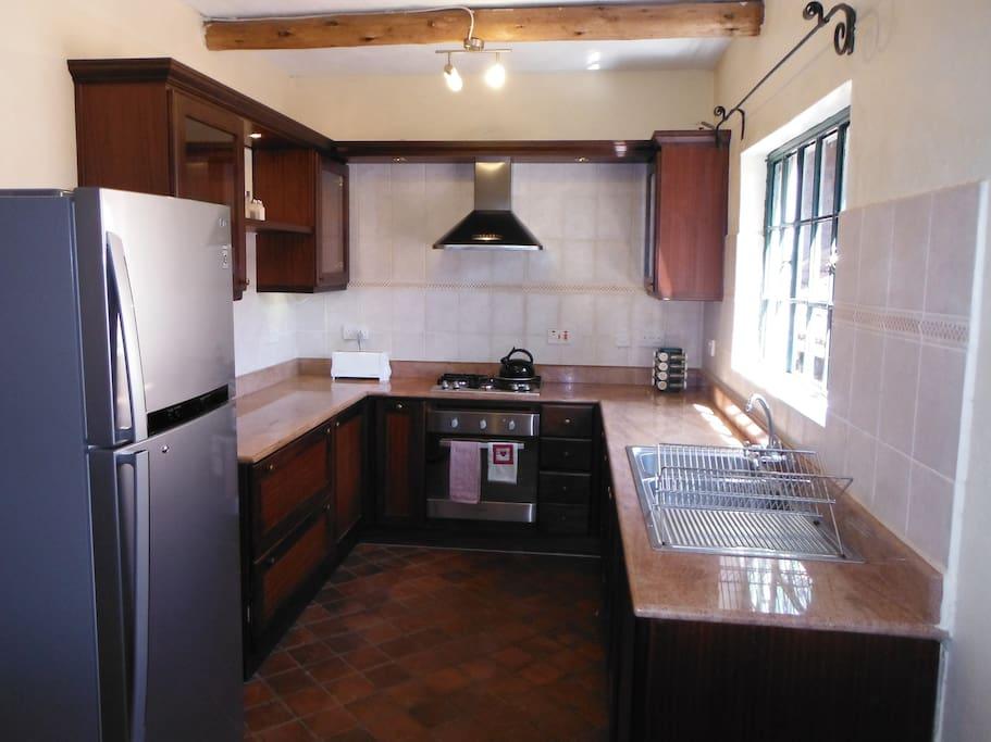 Full kitchen with gas stove, large fridge and dishwasher