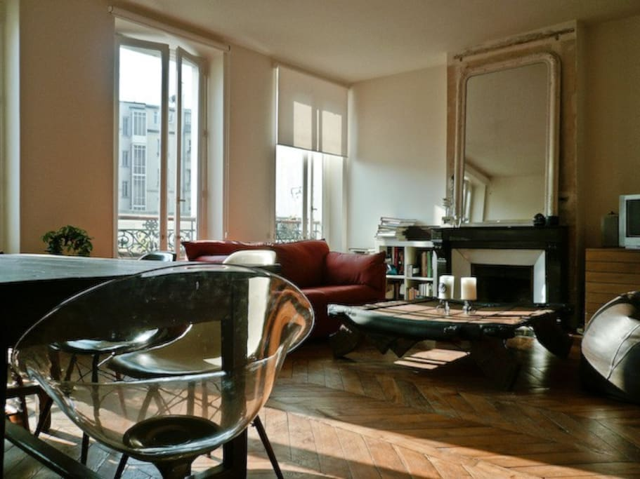 Authentic Parisian apartment with fireplace, wooden flooring and exposed beams.