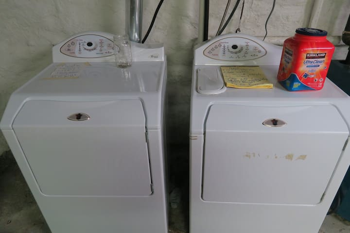 washer and dryer in basement with ironing board and iron