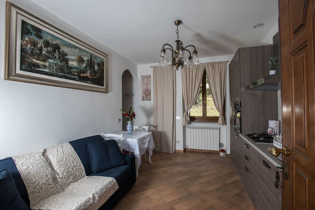 entrance of the apartment with a luxurious living room consisting of a high quality sofa, a very luxurious vintage setting, an elegant and romantic table with a vase with a bouquet of red roses and chairs with a bow made of tulle, equipped kitchen, coffee corner, windows overlooking the garden through curtains of high tailoring.
