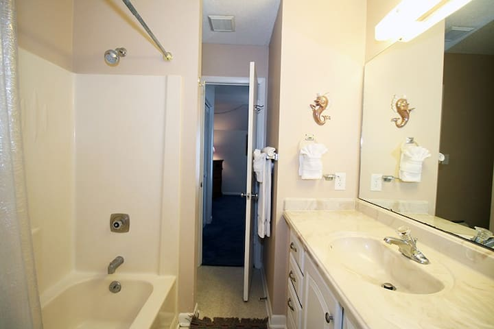 Connecting batroom between rooms 1 and 2 with a single sink basin and tub/shower combination