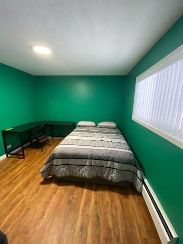 Queen bed with work desk in bedroom