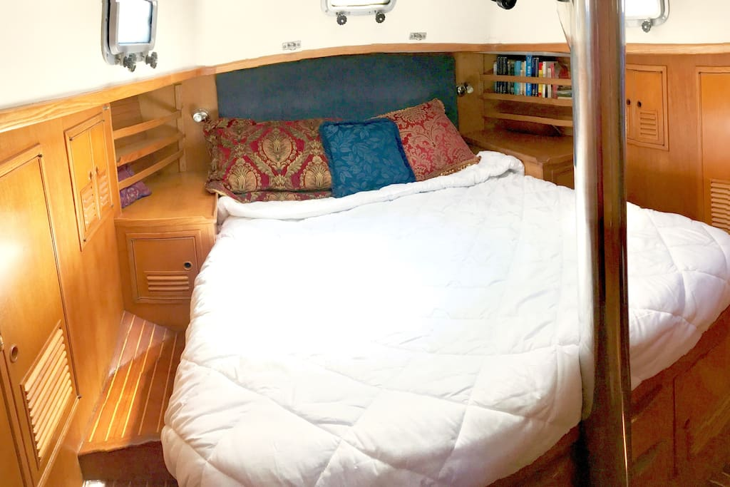 Queen berth in master stateroom. 5 opening portholes, and a large deck hatch overhead.