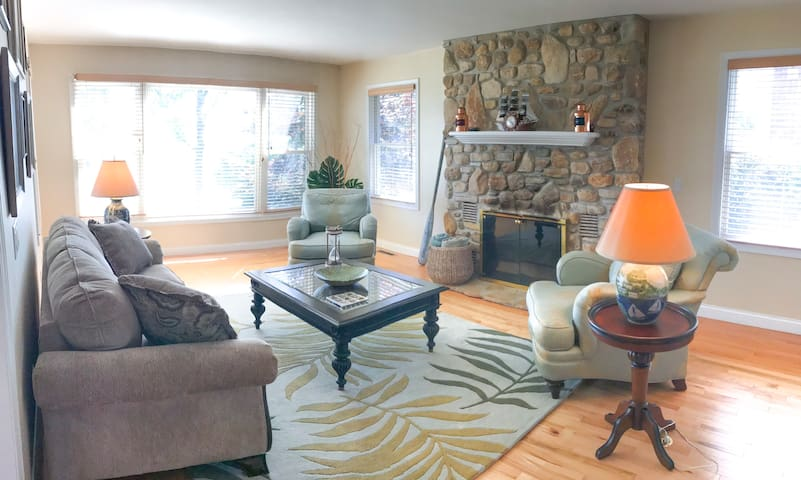 Living room with all around view of waterfront and gas fireplace.
