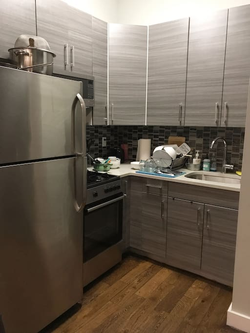 Modern full kitchen with gas stove and microwave.