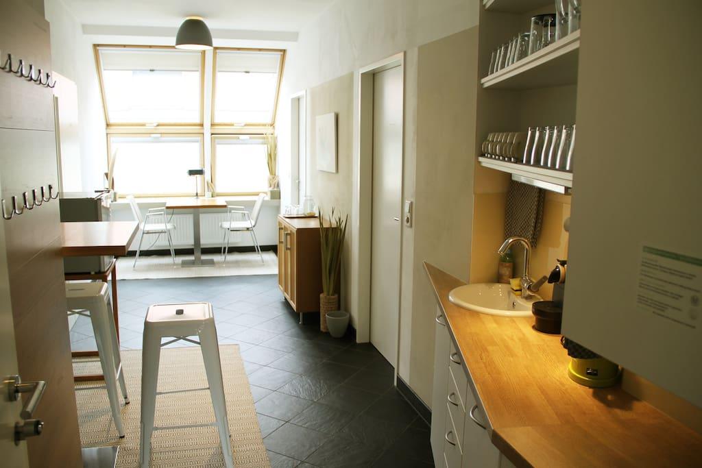 Minimalistische Küche mit Geschirr und kleinem Kühlschrank