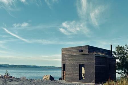 Lite arkitekttegnet hus rett ved sjøen