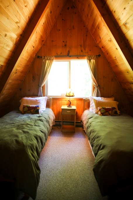 Upstairs enclosed loft has two single beds.