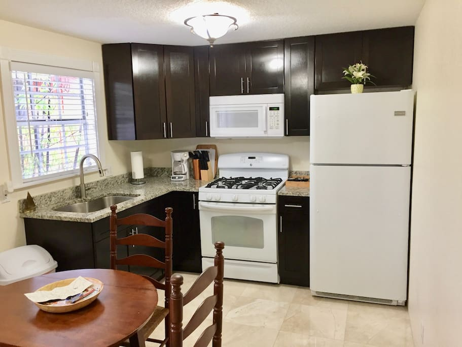 Full Size, Fully equipped eat in kitchen including set of pots, silverware, dish set, and towels.