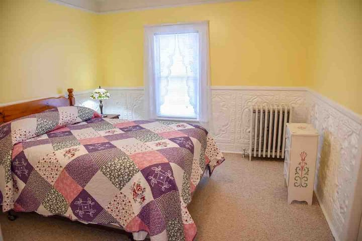 The yellow room has double bed and view of the patio/pool area.