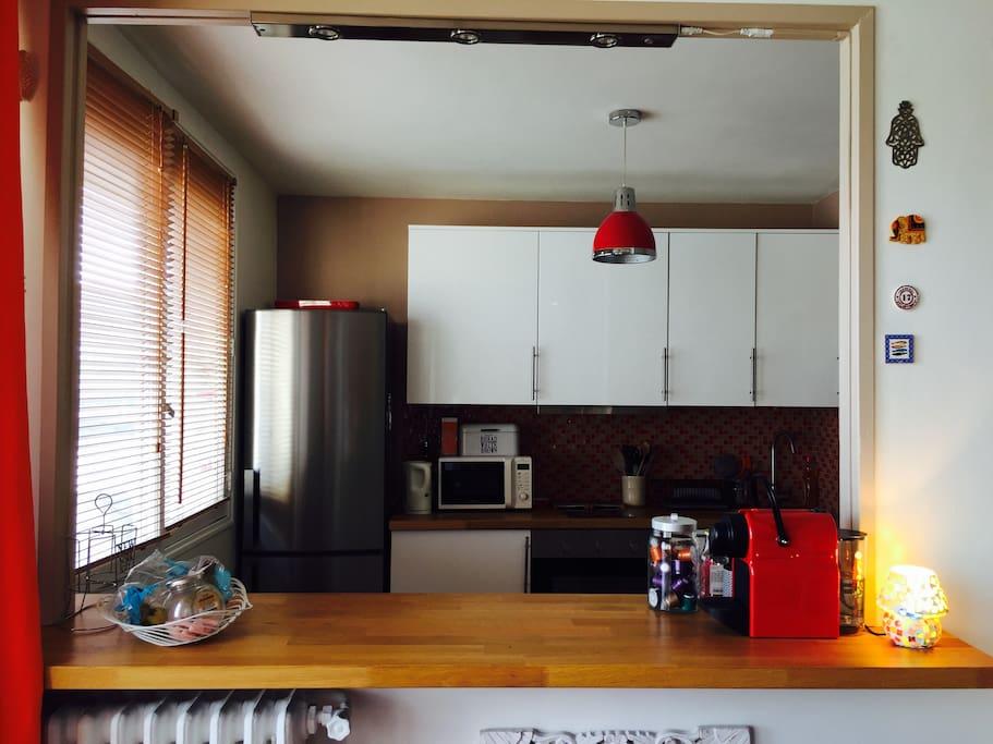 La cuisine vu du bar sur lequel vous pourrez profiter d'apéritifs. La cuisine est intégralement équipée: lave Linge séchant, four, plaques en céramique, lave vaisselle et machine Nespresso.