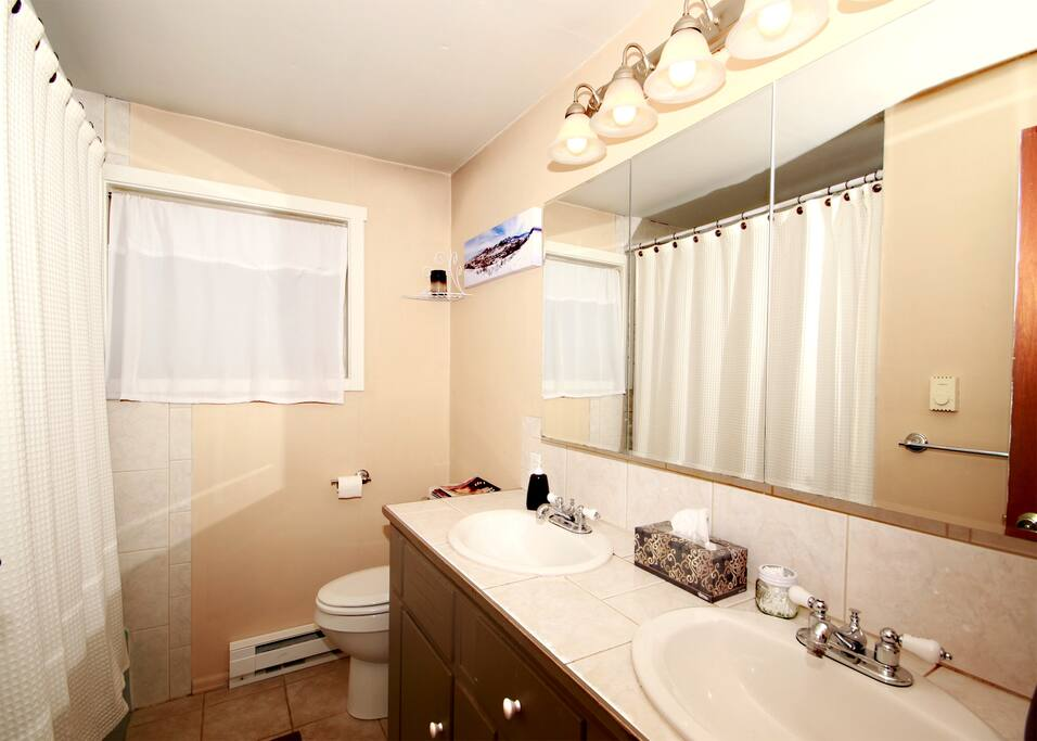 Bathroom with full bath and shower, and his and her sinks.