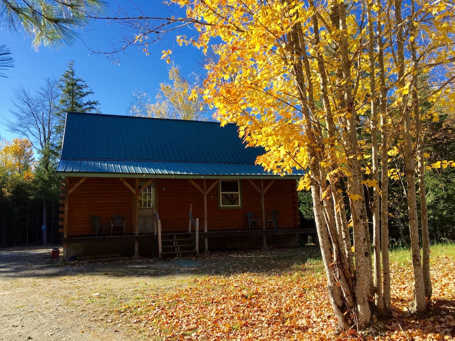 Log cabin with large front porch. Woods all around the open clearing for a private setting on seven acres.