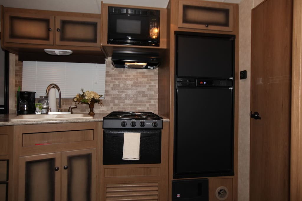 Gourmet kitchen with double-sided sink, gas range, microwave and refrigerator/freezer.