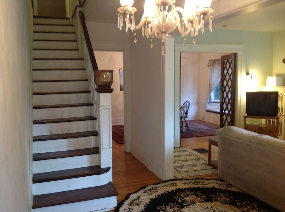 View from the entry hall of the front stairs, living room and dining room.