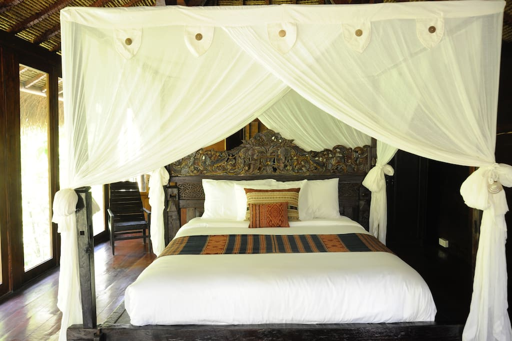 """Four poster Antique Balinese wooden bed, with new Italian Queen size mattresses. Adorned in luxurious bed linens + Heirloom-quality textiles from our friends at """"Threads of Life Bali""""."""