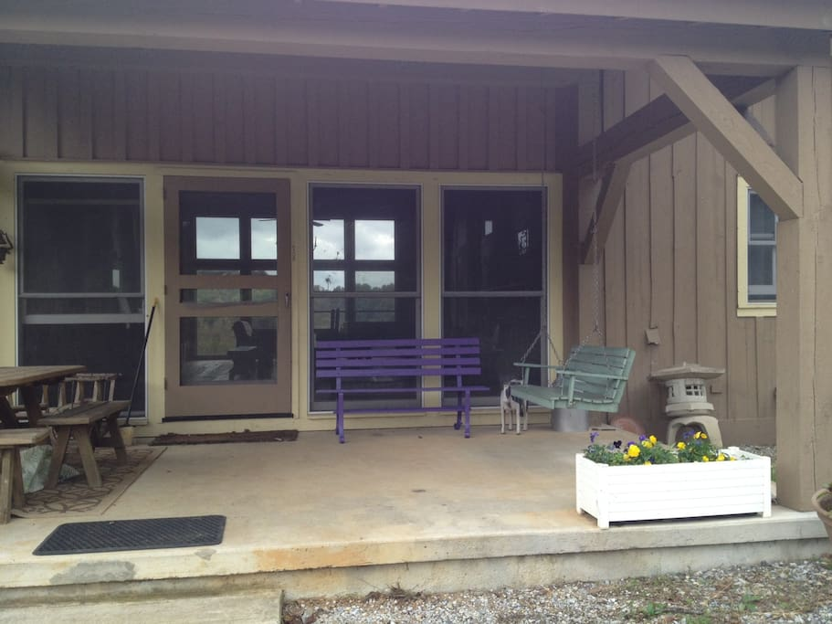 Front porch with picnic table, porch swing and bench.