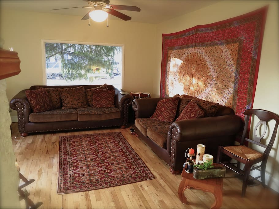 Our cozy living space with two windows, wood fireplace & tv...