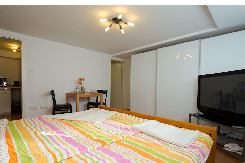 Großes Bett, großer Schrank, großer Fernseher. Links geht es zur Küche, rechts zum Bad.