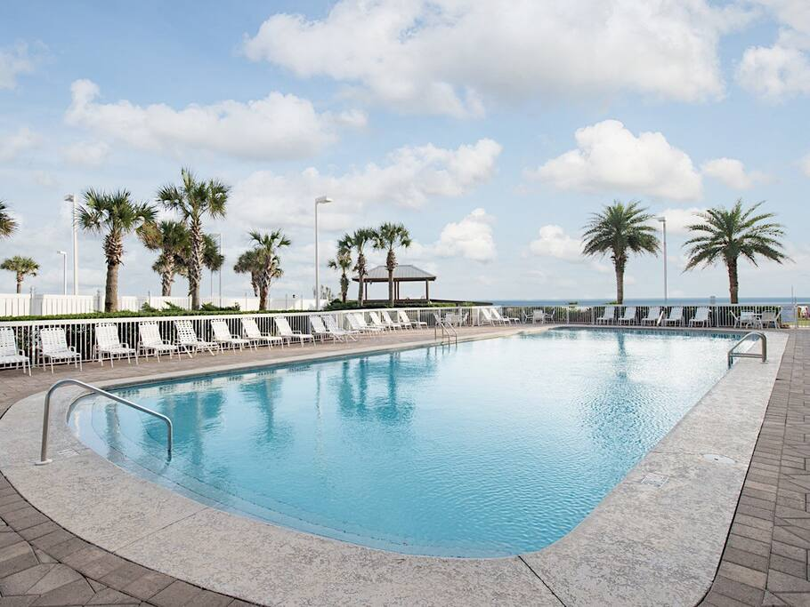 Lounge poolside under the palm trees with gulf breezes.