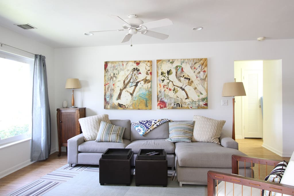 Exta-wide couch, Smart TV, smart art, and big windows make this one comfortable and sun-filled living room.
