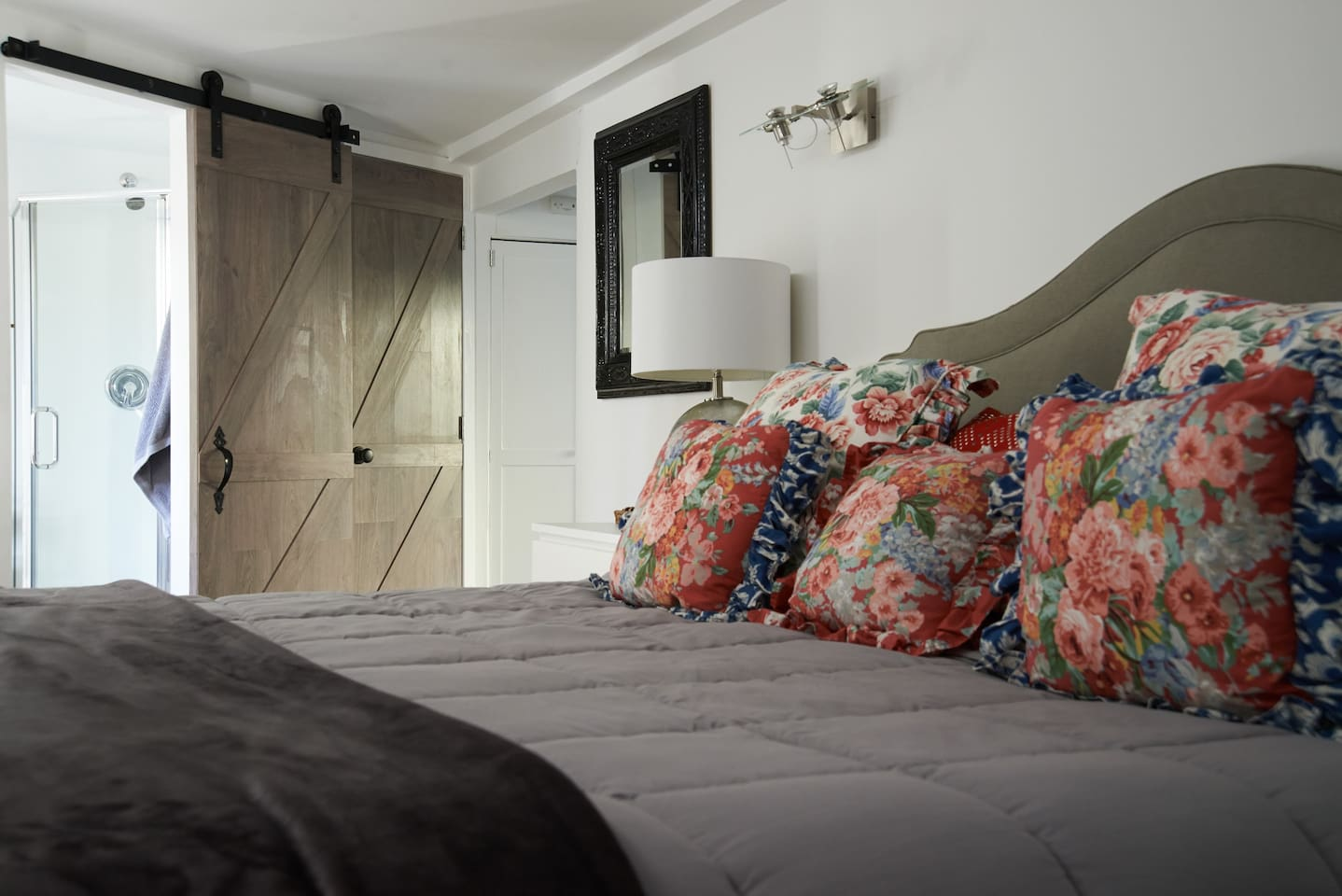 King size bed close to  bathroom with barn doors.