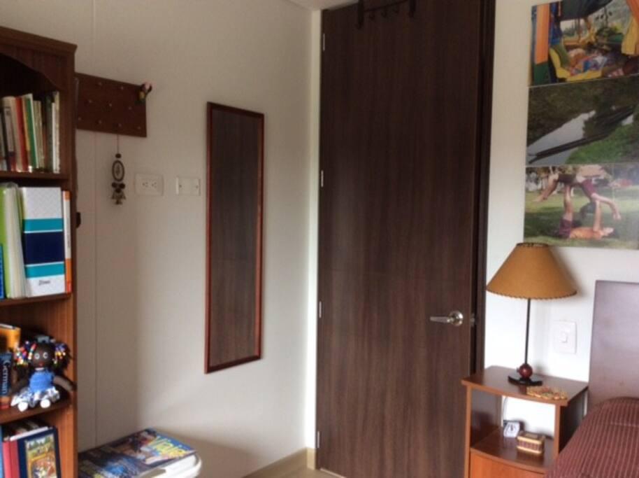Habitación amplia con mesa de noche, espejo, lámpara y libros disponibles.