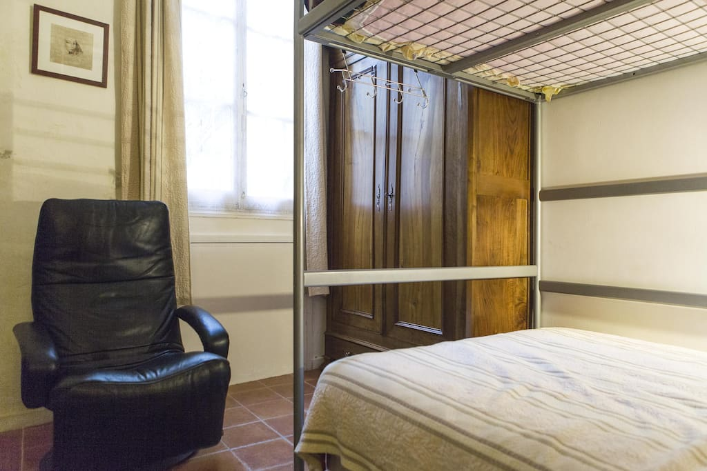 La chambre avec vue sur jardinet équipée de deux lits 140 cm dont un superposé, un bureau et une télévision, une table de repassage et un fer à repasser.