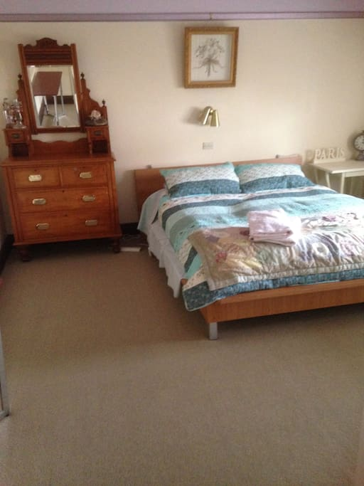 Main double bedroom with dresser, inbuilt wardrobe and mountain outlook.