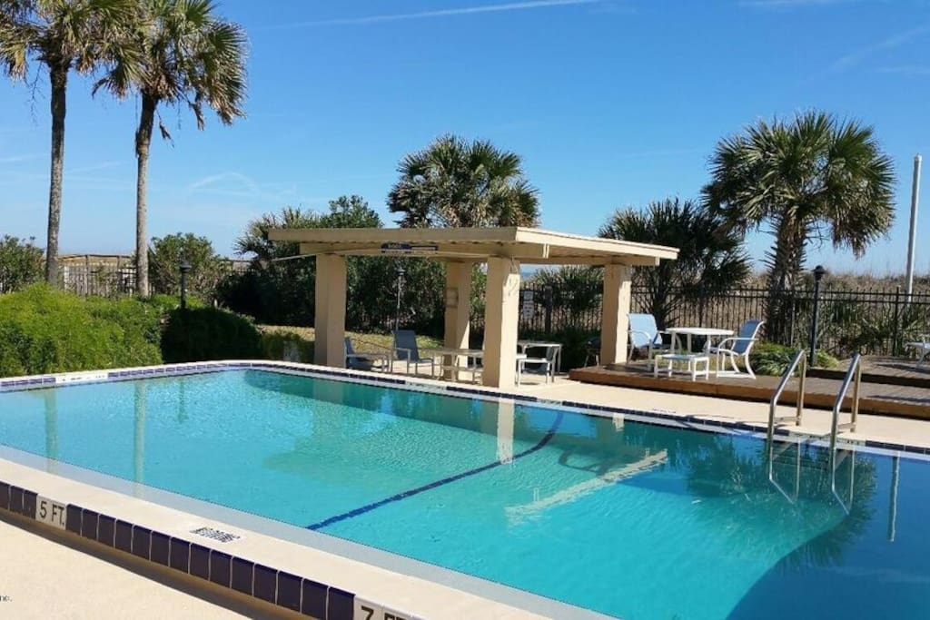 Gated Condo Pool with Chairs and Covered Picnic Area Adjacent to Ocean