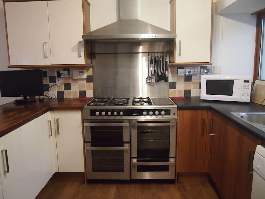 Open plan kitchen and dining area with loads of storage cupboards and plenty worktop space. Fantastic cooker which has a gas hob and electric oven.  Also has warming plate. Full size dishwasher, fridge freezer, microwave oven, electric kettle and 4 slice toaster.